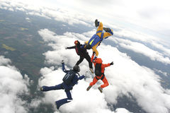 Four skydivers jump from a plane. With clouds in the background Royalty Free Stock Photography