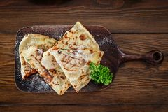 Four sliced wedges of meat and veggie filled quesadillas on cutting board. stock images