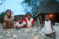 Four small black african girl resting on a stone fence. Stock Image