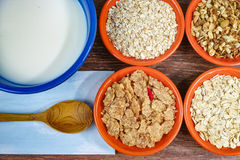 Four small bowls with different cereals and bowl with milk, healthy food Royalty Free Stock Photos