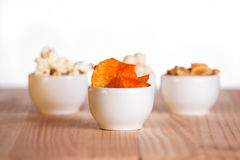 Four small bowls of snacks on natural wooden table. Royalty Free Stock Photography