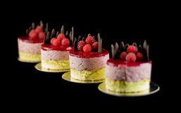Four small cakes with chocolate and raspberries Royalty Free Stock Images