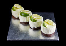 Four small cakes decorated with lime wedges Royalty Free Stock Image