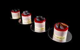Four small cakes decorated with plum wedges. Isolated on black Royalty Free Stock Image
