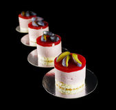 Four small cakes decorated with plum wedges. Isolated on black Stock Images
