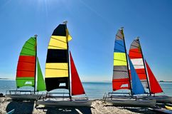 Four Small Catamarans with Brightly Colored Sails on a Key Biscayne Beach. Four small catamarans with brightly colored sails resting in the sand on a Key Royalty Free Stock Photos
