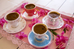 Four small cups of traditional foamy Turkish Coffee serving on a colorful flowery pink tray. On top of a white wooden table in low angle view Stock Image