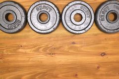 Weight plates. Four small dusty weight plates on a wooden table top Stock Photos