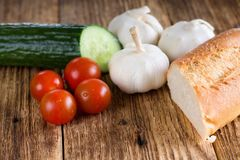 Four small tomatoes in front of baguette and other vegetable Royalty Free Stock Images