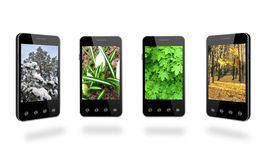 Four smart-phones with colored images of seasons Royalty Free Stock Images