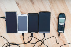 Four smartphones and one classic phone Royalty Free Stock Photography