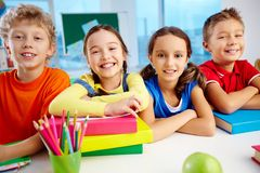 Four smiles. Portrait of cheerful school children flashing toothy smiles royalty free stock photography