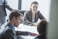 Four smiling business people sitting at a table and having a business meeting in the office Stock Photography
