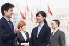 Four smiling business people talking outdoors in Beijing, china royalty free stock images