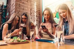 Four smiling female students sitting in cafeteria chatting using mobile phones Stock Image