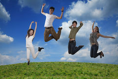 Four smiling friends jumping in mid-air, sky and cloud background Stock Photo