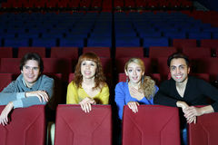 Four smiling friends sit on seats in cinema theater Royalty Free Stock Photography