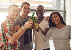 Four smiling friends tapping beer bottles Stock Photo