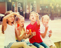 Four smiling kids blowing soap bubbles. Four smiling kids in school age sitting together and blowing soap bubbles Royalty Free Stock Images