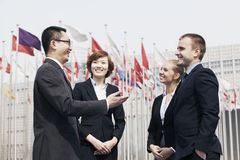 Four smiling multi-ethnic business people talking outdoors in Beijing, china Royalty Free Stock Images