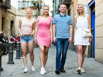 Four smiling persons walking together Royalty Free Stock Photos