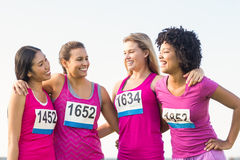 Four smiling runners supporting breast cancer marathon. In parkland Royalty Free Stock Photos