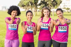 Four smiling runners supporting breast cancer marathon Stock Photo