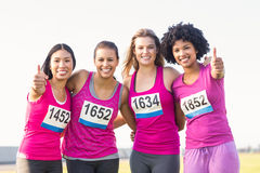 Four smiling runners supporting breast cancer marathon. Portrait of four smiling runners supporting breast cancer marathon in parkland Stock Images