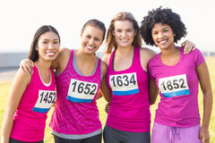 Four smiling runners supporting breast cancer marathon. Portrait of four smiling runners supporting breast cancer marathon in parkland Royalty Free Stock Image