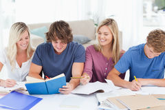 Four smiling students helping each other Royalty Free Stock Photography