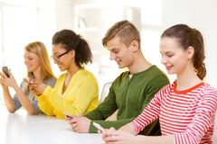 Four smiling students with smartphones at school. Education, technology and school concept - smiling students with smartphones at school royalty free stock image