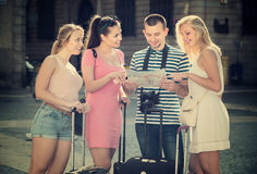 Four smiling traveling young people with map. Four smiling traveling young people searching for direction using paper map in town Royalty Free Stock Images