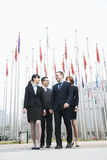 Four smiling young business people standing outside, flags flying in the background Royalty Free Stock Photo