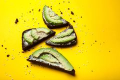 Four snacks of avocado slices on a yellow background royalty free stock photos