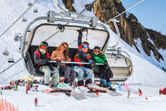 Four snowboard riders making fun on a chair lift Royalty Free Stock Photo