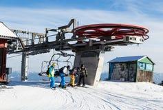 Four snowboarders descend to the ski chairlift. Four snowboarders descend to the ski chairlift at  ski resort. Kubinska Hola. Slovakia Royalty Free Stock Photos