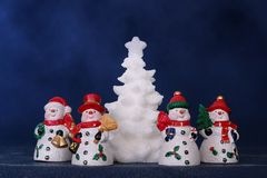Four snowmen and white xmas tree Stock Photos
