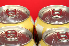 Four Soda Cans. Four yellow soda cans against a red background Stock Image