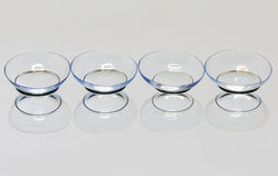 Soft contact lenses. Four soft contact lens on the mirror surface Royalty Free Stock Photo