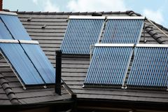 Four solar thermal tubes on rooftop Royalty Free Stock Photo