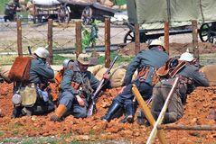 Four soldiers lay on the ground with guns. Stock Image
