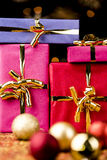 Four Solid Gift Boxes and Festive Spheres. Close-up shot of wrapped presents with golden bows. Tightly framed. Shallow depth of field. Blurred baubles in the Royalty Free Stock Image