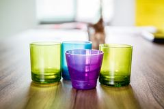Four solid plastic. Four solid plastic three color cups are violet, green and blue, placed on a brown wooden table. And the light from the window shines from Stock Photos