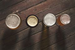 Four sorts of beer. Top view of a pale, dark, unfiltered pale and red fruit beer in four different beer glasses on a rustic wooden table Royalty Free Stock Photography