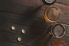 Four sorts of beer. Top view of pale, dark, unfiltered pale and red fruit beer in four different beer glasses on a rustic wooden table. Focus on the table and Royalty Free Stock Photo