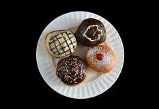 Four special sufganiyot with different icing on a white plate. Various sufganiyot with different icing and filling on a white plate royalty free stock image