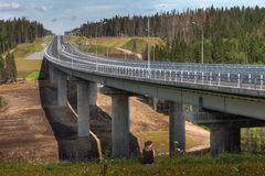 Four-speed road through forest, and steel motor road bridge. Stock Photos