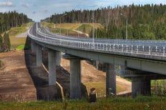 Four-speed road through forest, and steel motor road bridge. Saint Petersburg, Russia - August 7, 2015: Four-line speed highway St. Petersburg - Sortavala, in stock photos