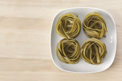 Four spniach pasta nests on a dish Royalty Free Stock Images
