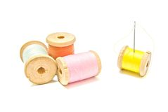 Four spools of thread with needle Royalty Free Stock Photos